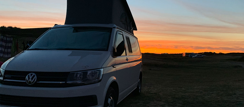 VW Bulli vor einem Sonnenuntergang an der Küste in Frankreich