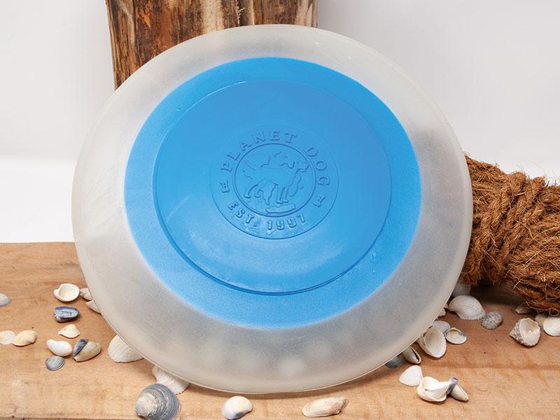 Hunde Frisbee Farbe blau leuchtet im Dunklen vor dekorativer Umgebung