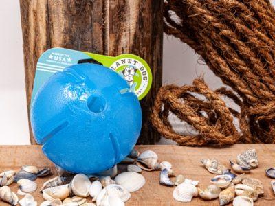 Snack Ball für den Hund vor dekorativem Hintergrund