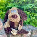 BoBo Bär Hundespielzeug sitzt auf einer Mauer